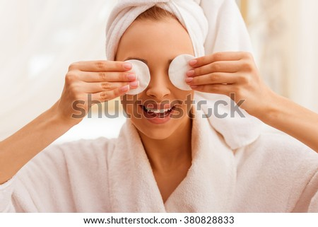 Portrait of beautiful young woman in a bathrobe with a towel on her head covering her eyes with sponges and smiling. - stock photo