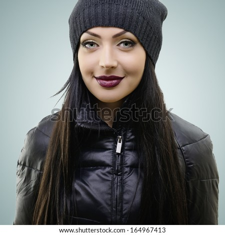 portrait of beautiful young woman in black hat and jacket, studio shot - stock photo