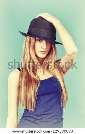 Portrait of beautiful young woman in black hat. Retro colour style photo. - stock photo