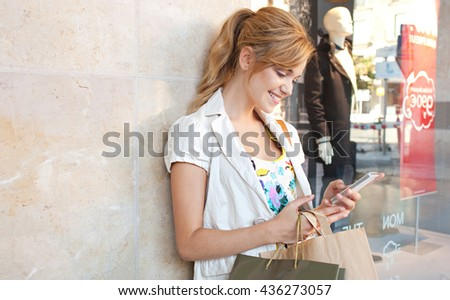 Portrait of beautiful young woman in city shopping street, smiling using smart phone to network outdoors. Tourist woman using technology, travel lifestyle. Shopping mall exterior with clothing store. - stock photo
