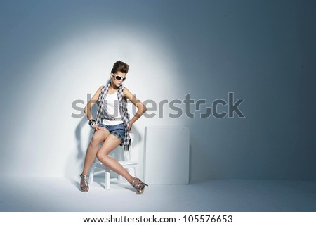 portrait of beautiful young woman in fancy dress sitting on chair in light background - stock photo