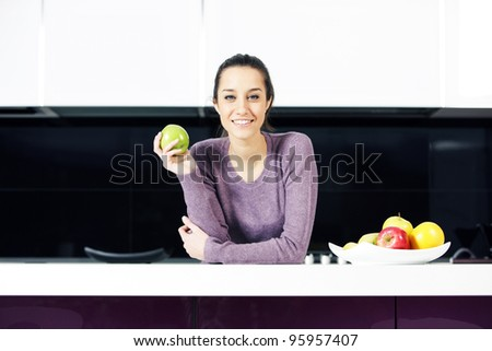 portrait of beautiful young woman in kitchen - stock photo