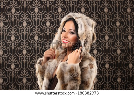 portrait of beautiful young woman in lingerie and fur coat posing against vintage background, photo of sexual beautiful girl is in fashion style - stock photo