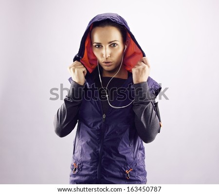Portrait of beautiful young woman in sportswear looking at camera. Confident female runner in hoodie against grey background - stock photo