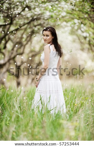 portrait of beautiful young woman in white dress walking in park - stock photo