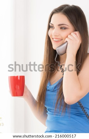Portrait of beautiful young woman laughing. Attractive brunette talking on phone and holding cup.  - stock photo