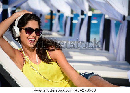 Portrait of beautiful young woman listening music on the beach - stock photo
