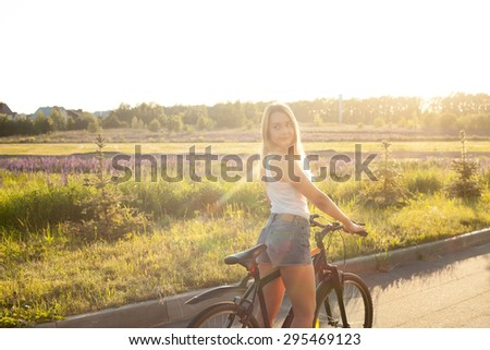 Portrait of beautiful young woman looking back sitting on mountain bike wearing casual white tank top and jeans shorts on countryside road on bright sunny summer day - stock photo
