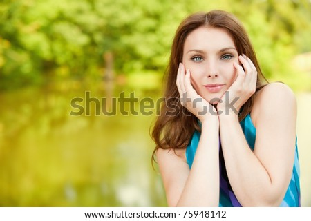 portrait of beautiful young woman on green background - stock photo