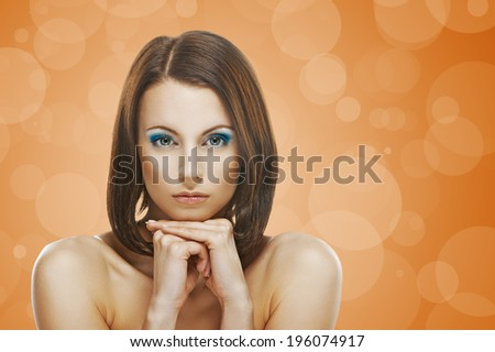 Portrait of beautiful young woman on orange background. - stock photo