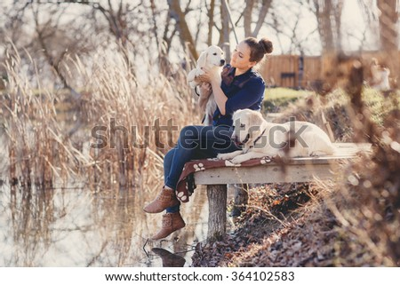 Portrait of beautiful young woman playing with dog by the river. portrait of Young girl sitting on the bridge with her dogs retrievers. woman with puppies. Girl with dogs. - stock photo
