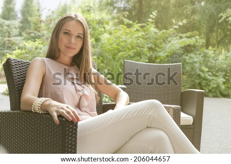 Portrait of beautiful young woman relaxing on chair in park - stock photo