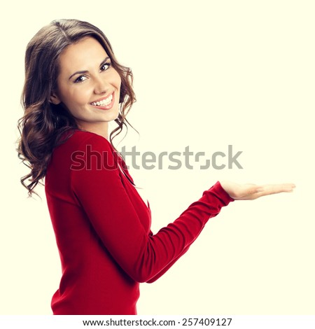 Portrait of beautiful young woman showing copyspace or something - stock photo