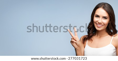 Portrait of beautiful young woman showing two fingers or victory gesture, on grey, with blank copyspace area for text or slogan - stock photo