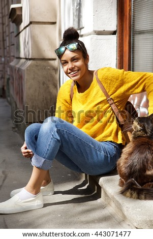 Portrait of beautiful young woman sitting by a street with cat - stock photo