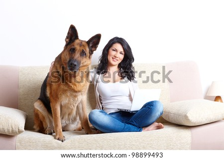 Portrait of beautiful young woman sitting on sofa with her german shepherd dog and netbook - stock photo