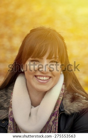 Portrait of beautiful young woman smiling outdoors in autumn  - stock photo