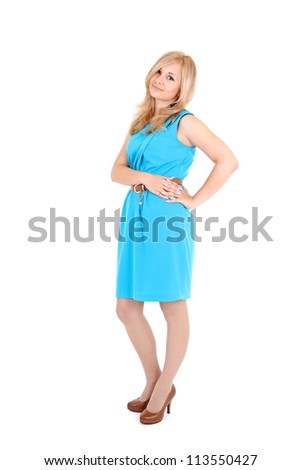 Portrait of beautiful young woman standing in blue dress - stock photo