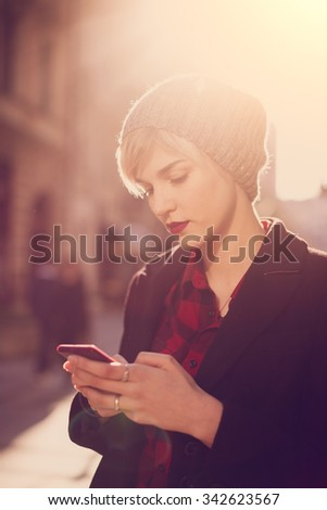 Portrait of beautiful young woman standing on the street and using her mobile phone  - stock photo