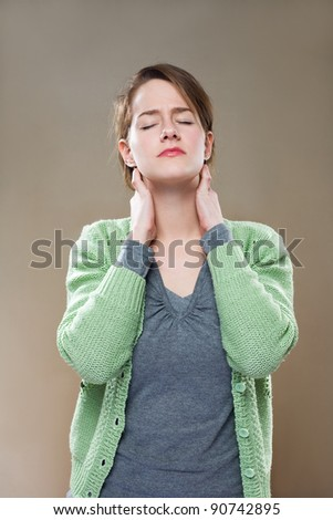 Portrait of beautiful young woman stressed out by neck pains. - stock photo