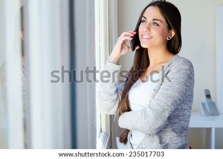 Portrait of beautiful young woman talking on the phone at home. - stock photo