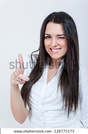 Portrait of beautiful young woman using her finger to show you. Attractive brunette in studio. - stock photo