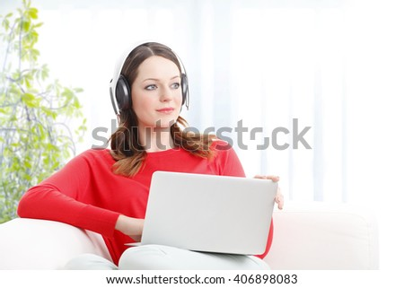 Portrait of beautiful young woman using laptop and listening music at home while relaxing on sofa. - stock photo