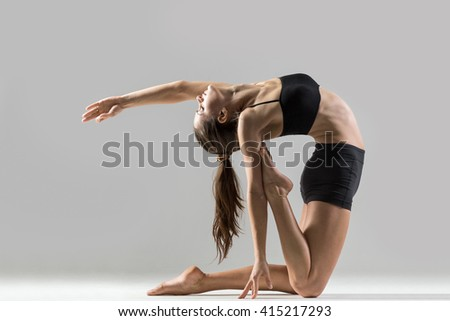 Portrait of beautiful young woman wearing black sportswear working out in studio. Fit sporty girl doing advanced yoga, pilates, fitness. Stretching with closed eyes. Ustrasana, Camel Posture - stock photo