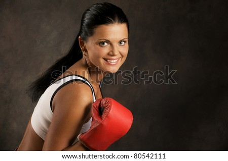 Portrait of beautiful young woman with a boxing glove. - stock photo