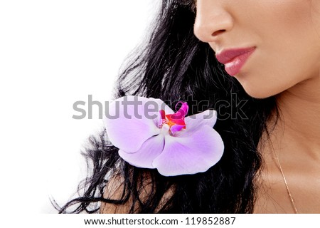 Portrait of beautiful young woman with an orchid flower on a shoulder - stock photo