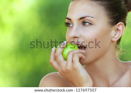 Portrait of beautiful young woman with apple, against background of summer green park. - stock photo