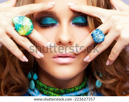 Portrait of beautiful young woman with bijouterie and curly hair touching her face by fingers - stock photo