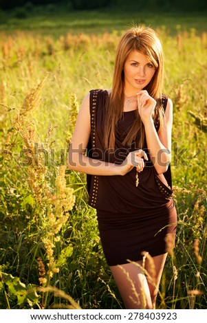 Portrait of beautiful young woman with blade of grass - stock photo