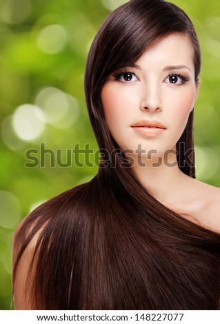 portrait of beautiful young woman with brown long hair over green background - stock photo