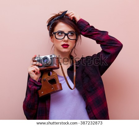 portrait of beautiful young woman with camera standing on the pink background - stock photo