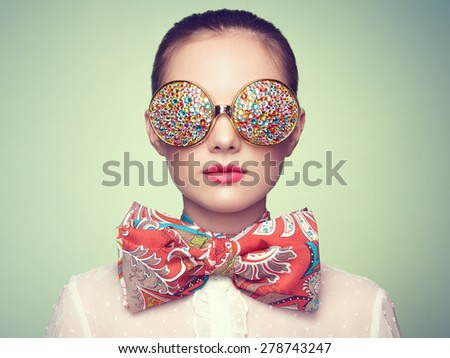 Portrait of beautiful young woman with colored glasses. Beauty fashion. Perfect make-up. Colorful decoration. Jewelry - stock photo