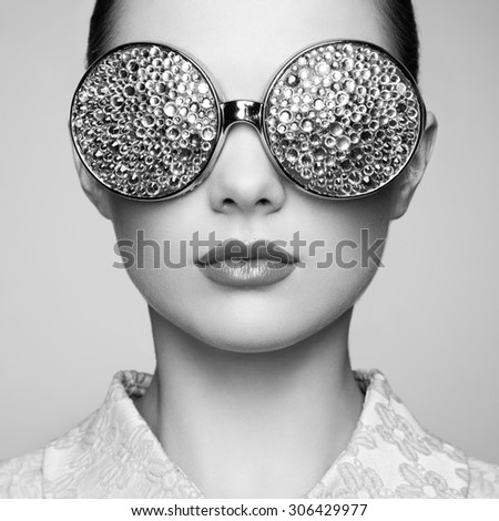 Portrait of beautiful young woman with colored glasses. Beauty fashion. Perfect make-up. Colorful decoration. Jewelry. Black and white - stock photo