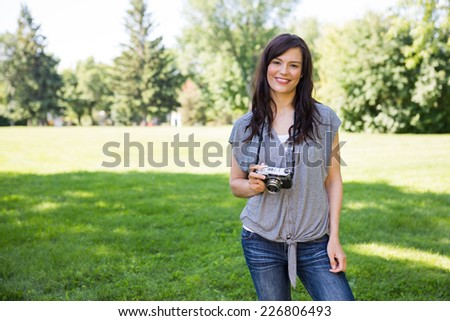 Portrait of beautiful young woman with digital camera in park - stock photo
