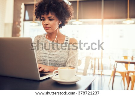 Portrait of beautiful young woman with earphones working on laptop while sitting at a coffee shop. African female at a cafe surfing internet on laptop. - stock photo
