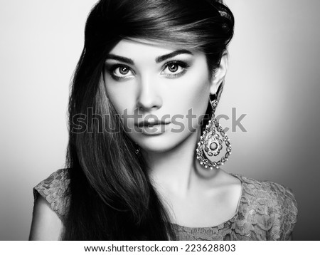 Portrait of beautiful young woman with earring. Jewelry and accessories. Perfect makeup. Fashion photo. Black and white - stock photo