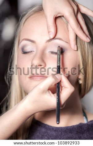 Portrait of beautiful young woman with esthetician making makeup eye shadow - stock photo