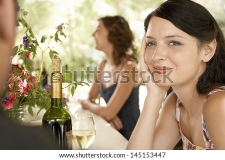 Portrait of beautiful young woman with friends at party - stock photo