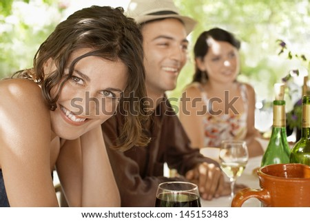 Portrait of beautiful young woman with friends enjoying drinks at party - stock photo