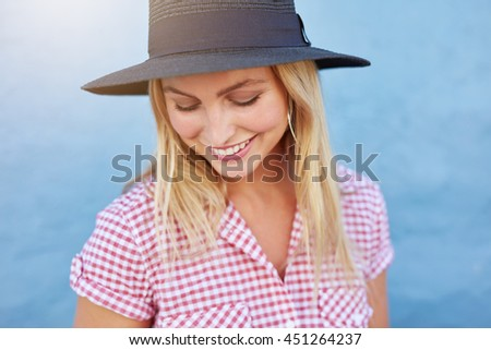 Portrait of beautiful young woman with hat looking down and smiling against blue wall. Caucasian female model looking happy. - stock photo