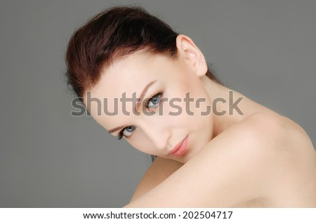 portrait of beautiful young woman with healthy clean skin on a face-gray background - stock photo