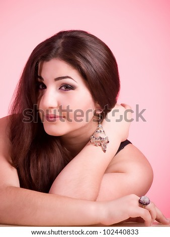 Portrait of beautiful young woman with jewelry on pink background - stock photo