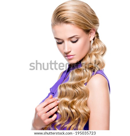 Portrait of beautiful young woman with long blond curly hair looking down - isolated on white background. - stock photo