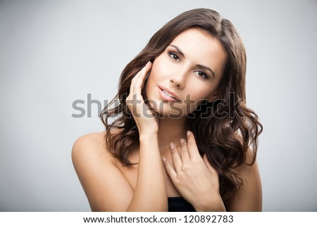 Portrait of beautiful young woman with long curly hair, over grey background - stock photo