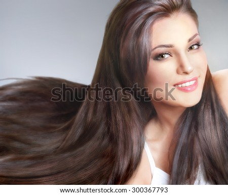 Portrait of beautiful young woman with long hair on gray background - stock photo