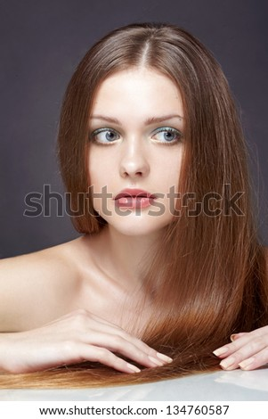 Portrait of beautiful young woman with long straight brown hair posing on black background - stock photo